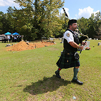 Kenneth Hiner of the Shelby County Sheriff's Office Pipes and Drum slowly walks away from the gravesite of former Lafayette County Sheriff Buddy East playing Amazing Grace to close the graveside service for east on Friday.