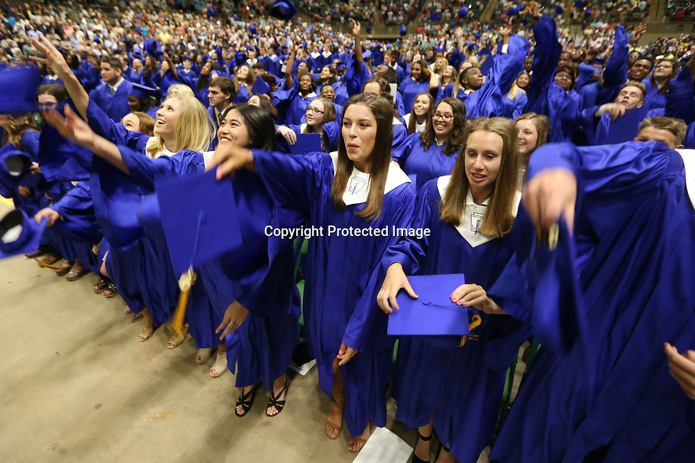 Tupelo High School graduates toss their caps into the air after graduation Friday night at the BancorpSouth Arena in Tupelo,