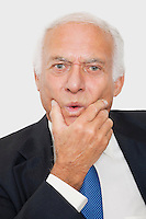 Portrait of suspicious elderly businessman against white background