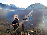 A builder takes a break as he smoke dries the walls of a guesthouse under construction in Upper Yubeng village. The village, cut off by mountains from the nearest road, is an ever-more popular tourist destination and guesthouses are beginning to outnumber traditional family houses and farms.