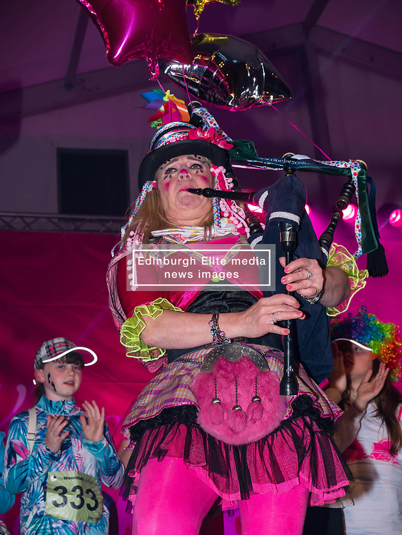 Pictured: Moonwalk Scotland, Edinburgh, Scotland, United Kingdom, 08 June 2019. The 14th Moonwalk Scotland 'Walk the Walk' night-time event with several thousand participants wearing specially decorated bras with a circus theme  to raise money and awareness for breast cancer causes. A piper entertains the crowd.<br /> <br /> Sally Anderson | EdinburghElitemedia.co.uk