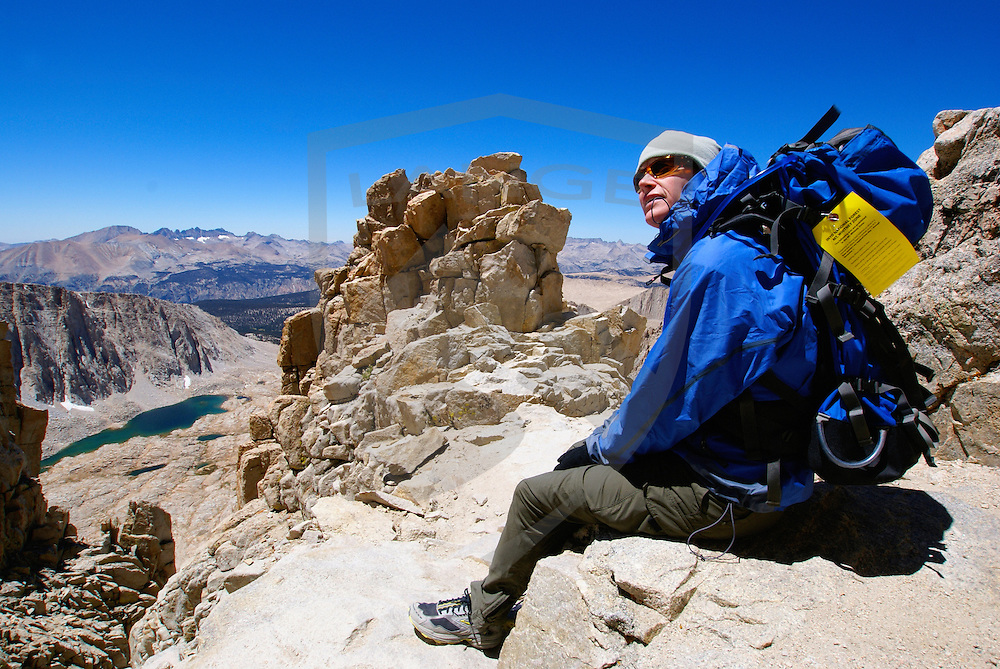 mountain hiker taking a break while hiking the sierra nevada mountain range high country of mount whitney california