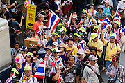 "05 JANUARY 2014 - BANGKOK, THAILAND: Anti-government protestors waving Thai flags and wearing ""Long Live the King"" headbands walk through the Little India neighborhood of Bangkok. Suthep Thaugsuband, leader of the anti-government protests in Bangkok, led the protestors on a march through the Chinatown district of Bangkok. Tens of thousands of people waving Thai flags and blowing whistles gridlocked what was already one of the most congested parts of the city. The march was intended to be a warm up to their plan by protestors to completely shut down Bangkok starting Jan. 13.     PHOTO BY JACK KURTZ"