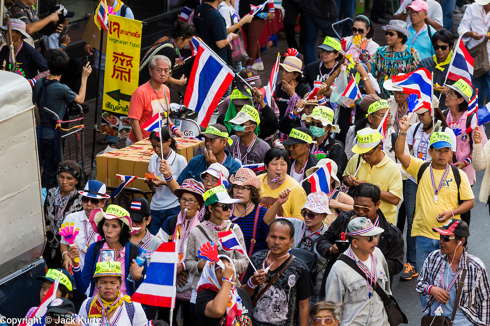 """05 JANUARY 2014 - BANGKOK, THAILAND: Anti-government protestors waving Thai flags and wearing """"Long Live the King"""" headbands walk through the Little India neighborhood of Bangkok. Suthep Thaugsuband, leader of the anti-government protests in Bangkok, led the protestors on a march through the Chinatown district of Bangkok. Tens of thousands of people waving Thai flags and blowing whistles gridlocked what was already one of the most congested parts of the city. The march was intended to be a warm up to their plan by protestors to completely shut down Bangkok starting Jan. 13.     PHOTO BY JACK KURTZ"""