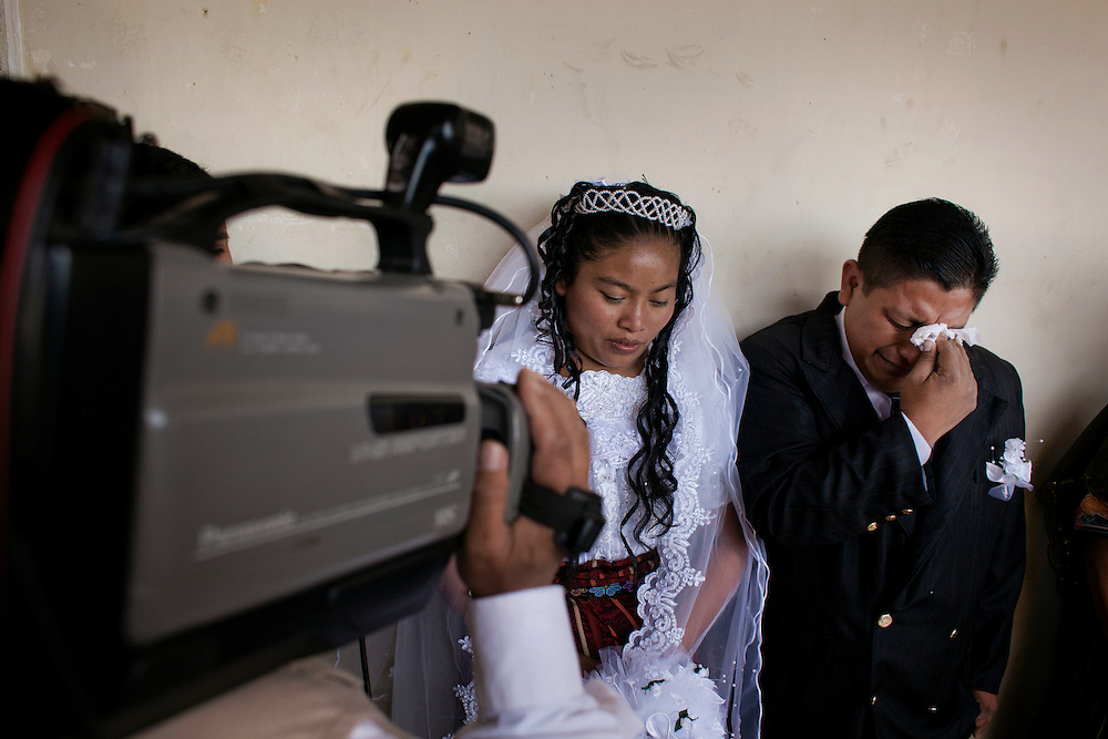 2012-01-28 Olintepeque, Guatemala. Wedding day in the village. Couples gather to marry at the city hall of Olintepeque. They are photographed and filmed before entering the hall to be married. A groom wipes some tears of emotions before entering. Photo: Markus Marcetic