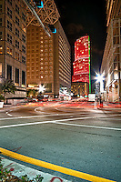 Night view of downtown Miami street corner with car light trails.