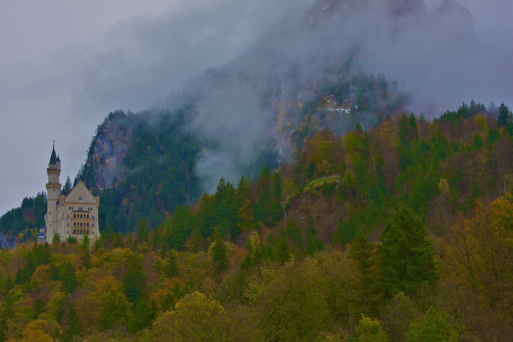 King Ludwig II's Neuschwanstein Castle on a cool fall day with a low cloud cover, giving the castle a sense of mystery and awe