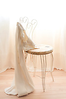 Beautiful, delicate embroidered cream coloured dress, draped over chair.