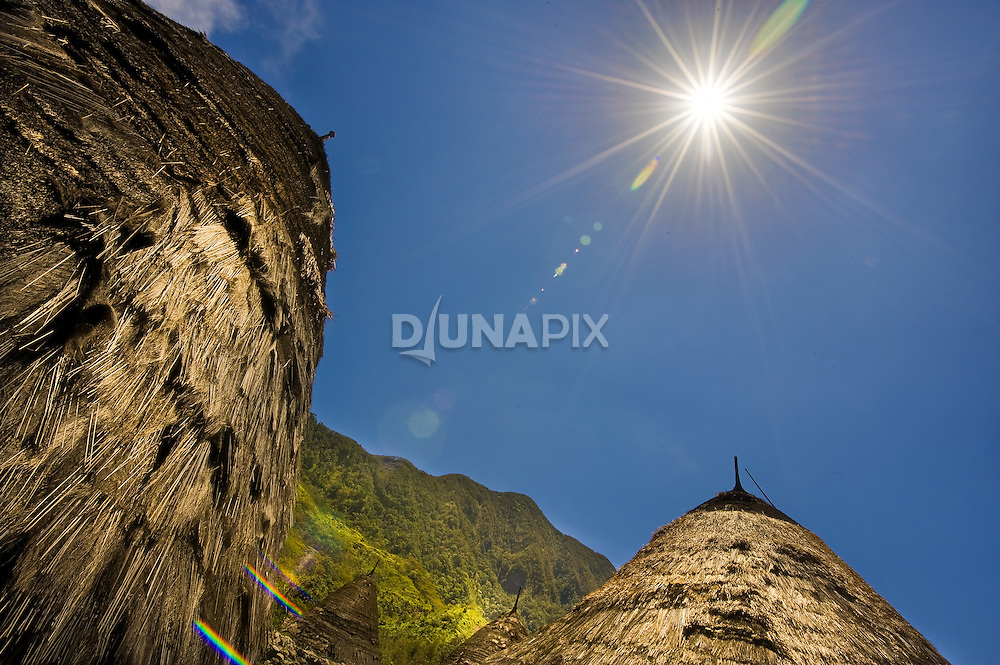 Sun star on raditional thatch-roofed homes, Wae Rebo, Manggarai, Flores.