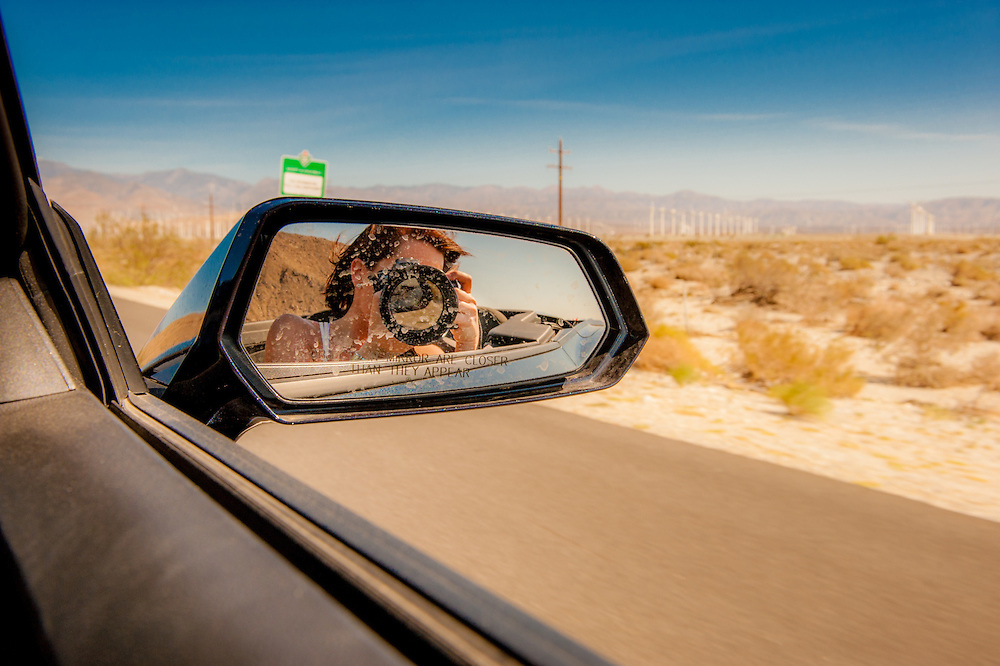 Young woman holding a camera is seen in the rear view mirror on a car near Palm Springs, California