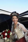 Bride with bouquet getting out of limousine