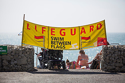© Licensed to London News Pictures. 26/08/2016. Brighton, UK. Lifeguards are stationed on the beach in Brighton to ensure the safety of all visitors to the seaside resort as members of the public take advantage of warm and sunny weather to spent time on the beach at the start of the August bank holiday weekend. Photo credit: Hugo Michiels/LNP