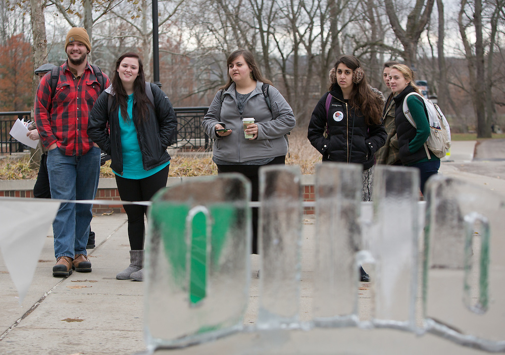 Students look on as ice carver Jeff Petercsak, of Rock on Ice, carves a penguin in front of Baker University Center on Dec. 3, 2014. A completed Ohio University ice sculpture sits in the foreground. Photo by Lauren Pond