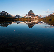 Sunrise at Two Medicine Lake with Sinopah Mountain reflected in the calm water - Glacier National Park
