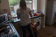 Victoria Cunningham prepares food for her son Oliver-James, as he cries at her side in the kitchen of the house the family rents in Bradford, Great Britain Monday, May 26, 2014. Through Save the Children's EAT, SLEEP, LEARN AND PLAY programme the family was awarded a fridge freezer and a toy and book pack. A record five million children in the UK could be trapped in poverty by 2020, according to new research by Save the Children. The report reveals that children have paid the highest price in the recession, with families having been hit by years of flat wages, cut to benefits and the rising cost of living. (Elizabeth Dalziel for Save the Children )