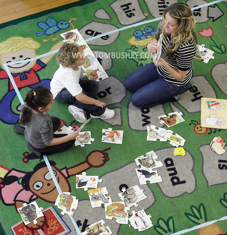 Teacher Lindsey Mitcheff helps Yaileen Jimenez, left, and Andreas Stephens with an alphabet puzzle in a Head Start class at North Congregational Church in Middletown on Sept. 25, 2012.