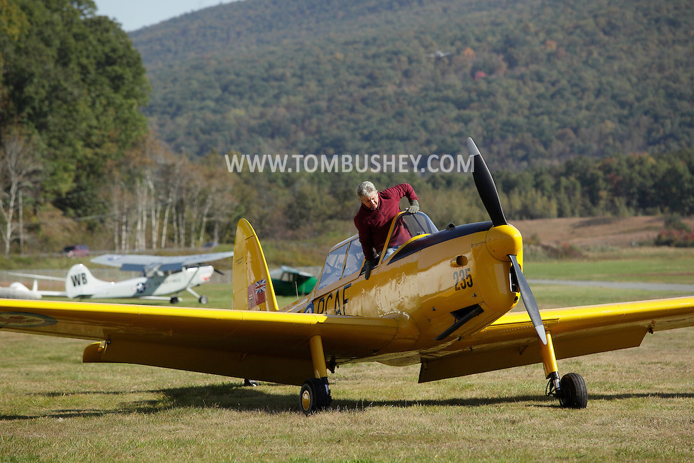 Wurtsboro, New York - A pilot climbs into a 1952 De havilland DHC-1 Chipmunk airplane on the runway during the annual Fly In - Drive- In Breakfast on Oct. 9, 2011.