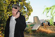 SUN-STAR PHOTO BY BEA AHBECK<br /> Pilot James Drexler, of Fairfiled, makes a phone call after he successfully put the plane he was flying down just off Hw 99 close to Le Grand Friday evening, June 18, 2010. He reported he lost the pitch control of the plane.