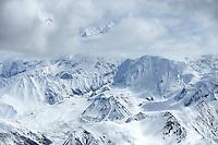 Paragliding pilot Dave Turner flying by Denali during the Alaska paragliding traverse. Alaska Range, Alaska.