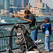 Family fishing in the Hudson River from Battery Park, Lower Manhattan, New York, NY