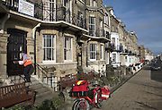 Postman delivering mail, Seafront guest houses out of season, Lowestoft, Suffolk, England