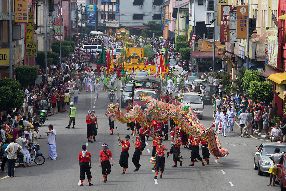 © Licensed to London News Pictures. 28/09/2014. Ipoh, Malaysia. A dragon dance along a street as devotees process with deities through the streets of central Ipoh, Malaysia on the 5th day of the Nine Emperor Gods Festival, Sunday, Sept. 28, 2014. The festival is a nine-day Taoist celebration to mark the birth of the Nine Emperor Gods from the first day to the ninth day of the ninth moon in Chinese Lunar Calender. The origin of the Nine Emperor Gods (stars of the Northern constellation) can be traced back to the Taoist worship of the Northern constellation during Qin and Han Dynasty and absorb this practice of worshipping the stars and began to deitify them as Gods. Photo credit : Sang Tan/LNP