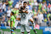 New England Revolution midfielder Gustavo Buo (7) celebrates with forward Teal Bunbury (10) after a goal during a MLS soccer game, Saturday, Aug. 10, 2019, in Seattle.  The teams played to a 3-3 tie. (Alika Jenner/Image of Sport)
