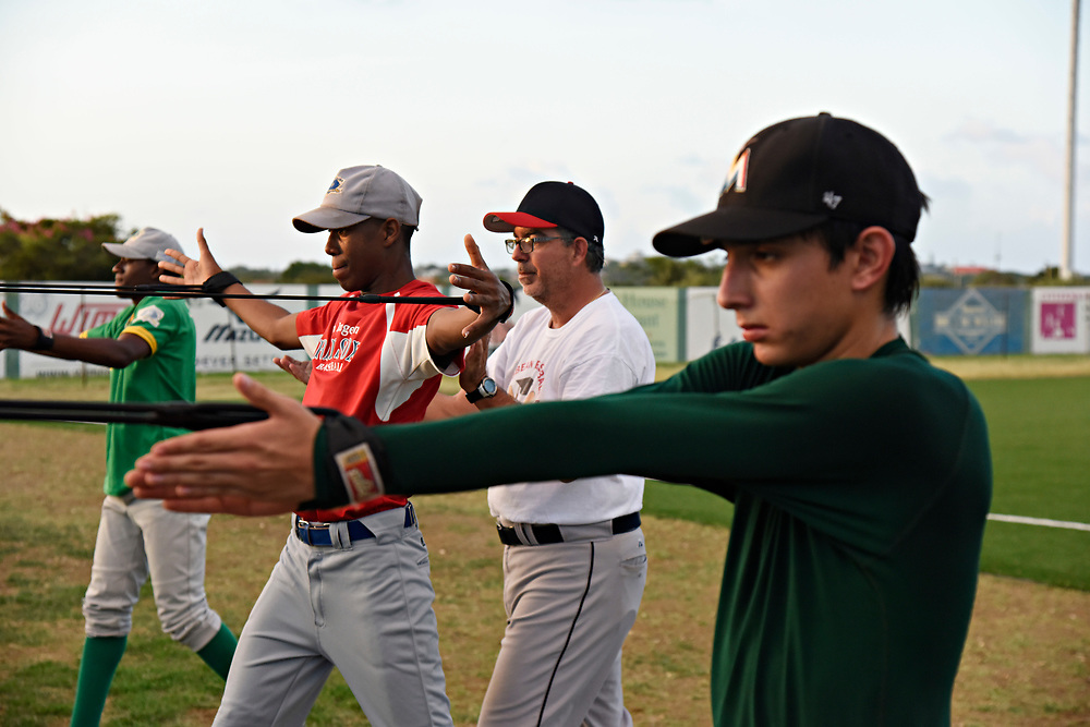 WILLEMSTAD, CURACAO - DECEMBER 11, 2014: Some of Curacao's best senior league players are put through drills for development at the Dutch Caribbean Baseball Academy in Santa Rosa to make them more viable for American college baseball programs as well as the major leagues. Pitching coach Fermin Coronel (cq), center, who is also the third base coach for the Dutch National Team, puts his young pitchers through a series of stretches to warm up all the muscles needed to throw well. (photo by Melissa Lyttle)