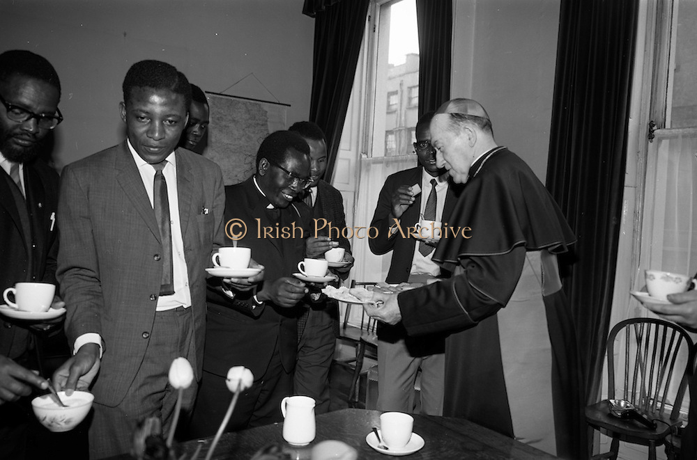 """06/05/1965<br /> 05/06/1965<br /> 06 May 1965<br /> African Students on a visit to Dublin. A group of African students of Catholic Sociology from Claver House, London, on an educational holiday to Ireland. The group stayed with Irish families under the auspices of """"Le Cheile"""" a group that promoted friendship and exchange of culture between Irish and overseas people. the students were entertained by His Grace, Most Rev. Dr. McQuaid, Archbishop of Dublin to a visit to the Dublin Institute of Catholic Sociology. Photo Shows the Archbishop entertaining the visitors  to tea and offering Fr. Stefan Haule (Tanzania) a biscuit."""