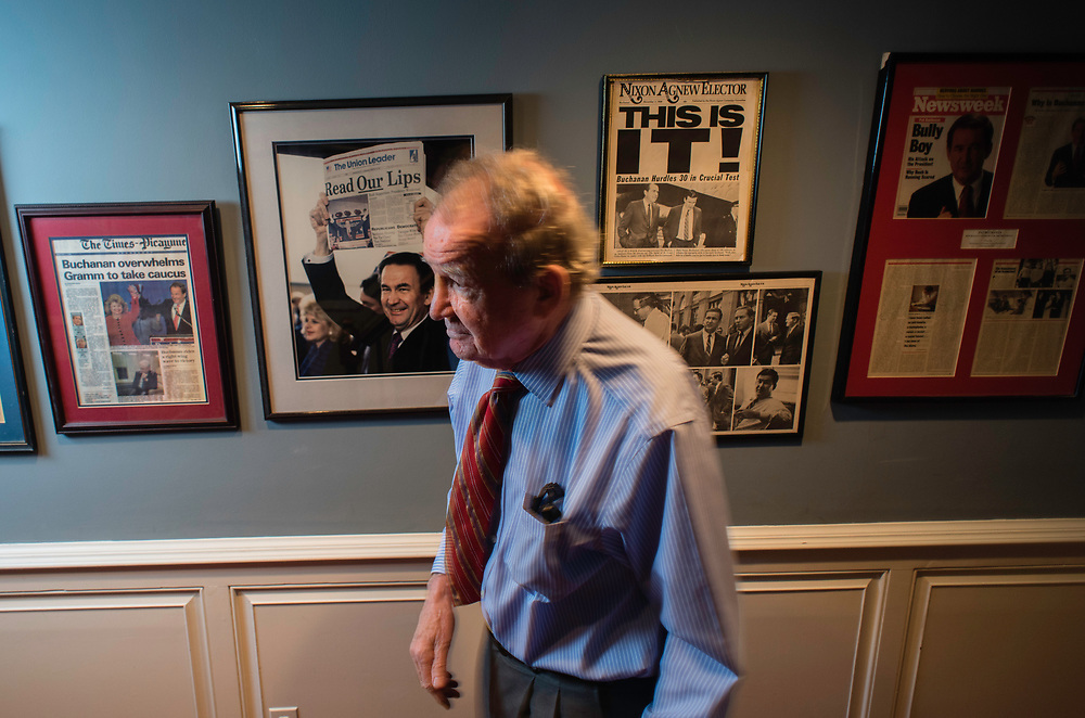 MCLEAN, VA -- 3/21/17 -- Buchanan walks past the younger version of himself in the hallway leading to his office. Buchanan keeps some framed memorabilia from his political career on display. Respected conservative commentator Pat Buchanan reflects on his career at his home in McLean. .…by André Chung #_AC24136