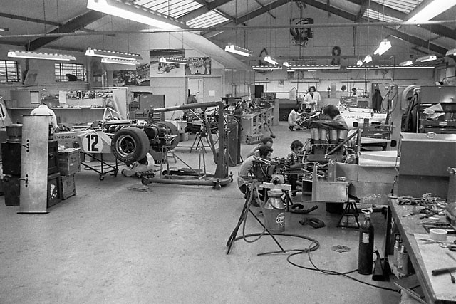 McLaren race shop at Colnbrook, UK, circa May 1972. Mechanics Jim Stone and Vince Higgins and designer Gordon Coppuck confer behind M20 Can-Am car.