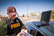21 SEPTEMBER 2010 - PHOENIX, AZ:  Detective Scott Thompson (CQ) checks paperwork after participating in the arrest of Fernando Dick (CQ) in Phoenix Tuesday. Crime has steadily dropped in Phoenix over the past few years, in line with national trends. The latest number released this month showed Phoenix reported fewer 2010 homicides, rapes, robberies, thefts - in addition to other major crimes -- compared with the same time period the previous year. Detectives in the Phoenix police department's Major Offender Unit make several arrests every day.   PHOTO BY JACK KURTZ