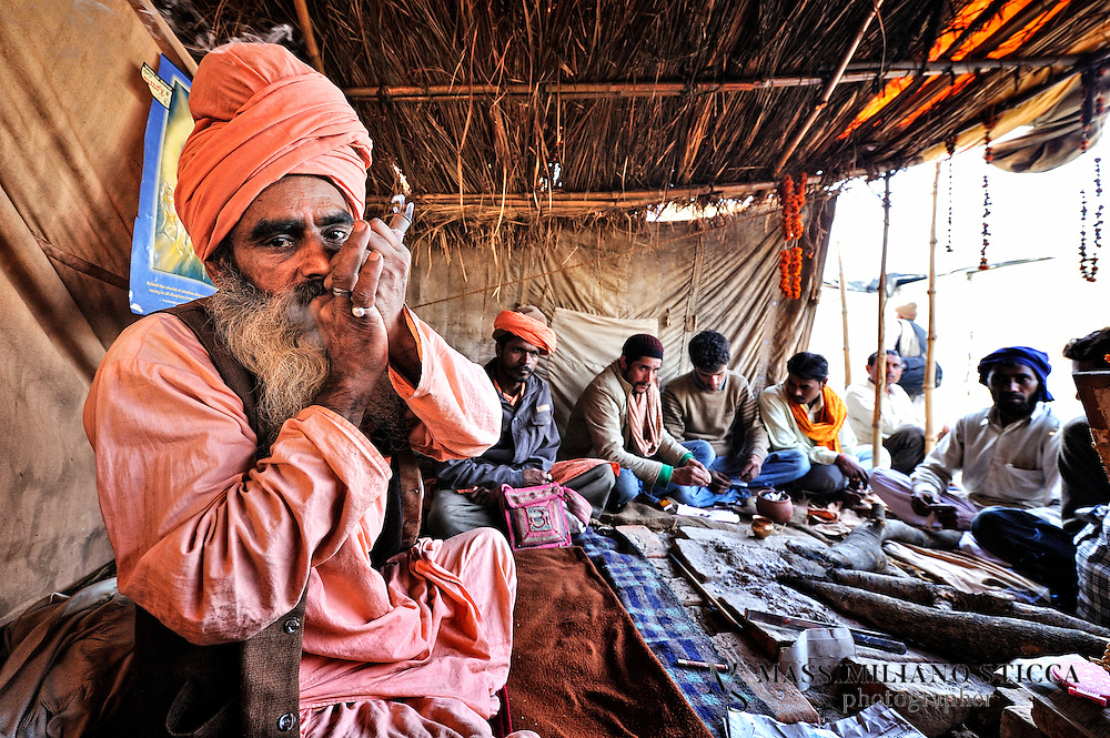 A Sadhu smoking chillum during the Kumbh Mela..The Indian Sadhu's (holy men) have been smoking chillums for thousands of years, and the spiritual meaning of this is comparable to the drinking of red wine by Catholics. At their rituals, the chillum is prepared with a combination of charas (herbs) and tobacco. Through a Hindu ceremony, the Hindu god Shiva was called upon, the Sadhus believing that Shiva would enter into the smoker. In the ceremony, a wet Safi cloth is used, a stone inserted, and the mixture placed into the chillum. The chillum's mouth piece is cupped in two hands and forms a closed prism, as the smoker inhales the smoke without the lips touching the pipe. He puffs violently to light the chillum sufficiently to be passed to the person to the right. In the ceremony of the Jamaican Rastas, the chillum used is made of a cow's horn and wood..