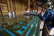The Citadel. Imperial Enclosure. Thai Hoa Palace (Palace of Supreme Harmony). Tourists with model of the Imperial Palace.