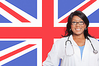 Portrait of confident mixed race female surgeon over British flag