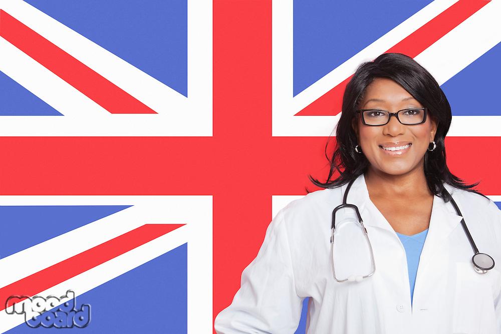 Portrait of confident mixed race female surgeon over British flag