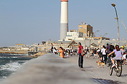Israel, Tel Aviv, people having fun at the renovated promenade in the old port, now an entertainment centre The Reading powerplant in the background