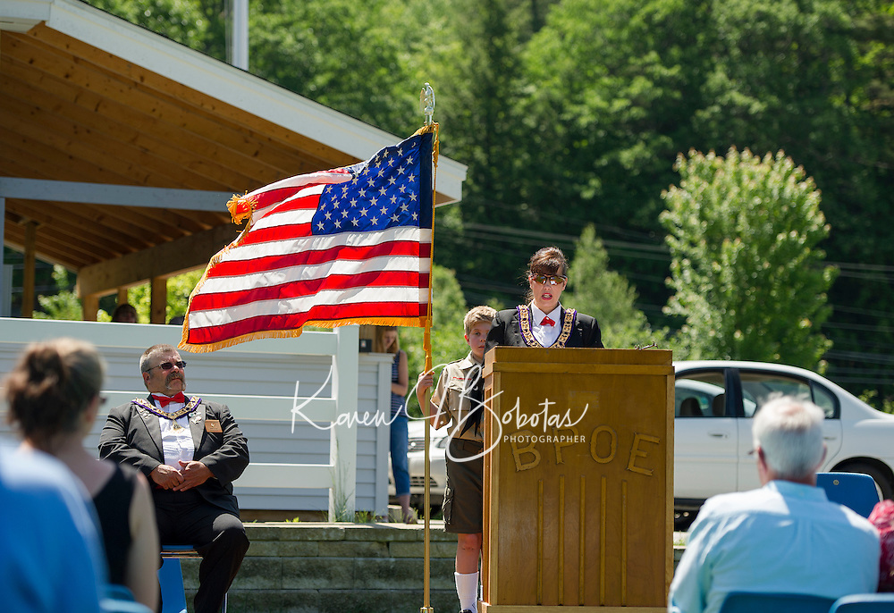 Elks Esquire Dotti Gath gives a history of our flag from the podium at the Elks Lodge on Sunday morning during Flag Day ceremonies.  Seated is Exalted Ruler Jim Culpon and holding flag is Adam Barton Boy Scout Troup 68.  (Karen Bobotas/for the Laconia Daily Sun)