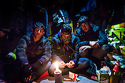 CALAIS, FRANCE - JAN 16: Young men from Afghanistan keep warm inside a hut in the Calais refugee camp known as 'the jungle' on January 16, 2016