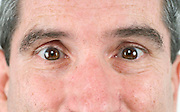 close up of a middle aged man's face with eyes wide open