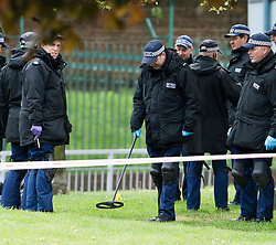 © London News Pictures. 23/05/2013. Woolwich, UK. A police search using a metal detector to search an area of  grass at the scene in Woolwich, London where a member of the armed forces was attacked yesterday (22/05/2013) by two men in what is being described as a terrorist attack. Photo credit: Ben Cawthra