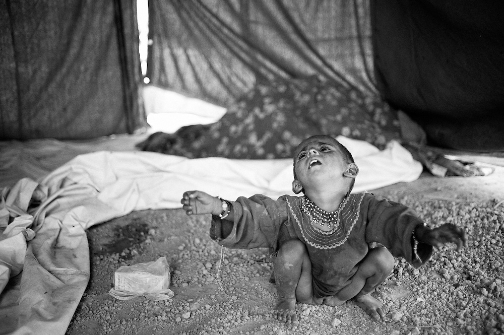 A young girl sits on the sandy floor crying for her mother to pick her up in one of the many camps set up to accomodate flood victims. Khaipur, Paksitan, 2010