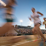 The 2014 USA Track and Field  Championships in Sacramento:  Women's 10000 meter final-  Athletes run by the Hornet Stadium grandstand.