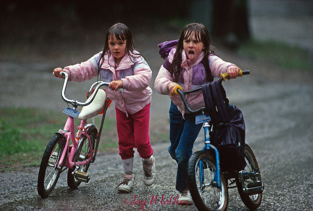Valerie Willitts, left and her sister Stephanie Willitts, push heir bikes up a hill in a rainstorm toward their home in Yosemite valley after school.  March 1989.