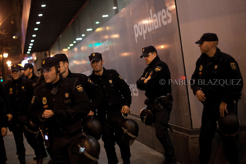 Riot police stand outside the PP headquarters, before a demonstration takes place to protest against corruption and to claim Mariano Rajoy to resign, in Madrid on January 31, 2013. The Spanish Newspaper 'El Pais' published secret papers of income implicating Spanish Prime Minister and other members of the PP (Popular Party). Rajoy's government has denied these secret payments.