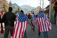Men wearing USA flags run through the town plaza during the 2010 Olympic Winter Games in Whistler, BC Canada