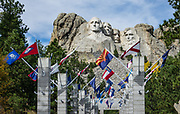 State flags at Mount Rushmore National Memorial, Keystone, South Dakota, USA. Sculptor Gutzon Borglum designed and oversaw the project 1927–1941, with help from his son, Lincoln Borglum. Mount Rushmore features 60-foot sculptures of the heads of four United States presidents: George Washington (1732–1799), Thomas Jefferson (1743–1826), Theodore Roosevelt (1858–1919), and Abraham Lincoln (1809–1865). South Dakota historian Doane Robinson conceived the idea of carving the likenesses of famous people into the Black Hills in order to promote tourism. Robinson's initial idea of sculpting the Needles was rejected by Gutzon Borglum due to poor granite quality and strong opposition from Native American groups. They settled on Mount Rushmore, and Borglum decided on the four presidents. Each president was originally to be depicted from head to waist, but lack of funding ended construction in late October 1941. Mount Rushmore is a batholith (massive intrusive igneous rock) rising to 5725 feet elevation in the Black Hills.