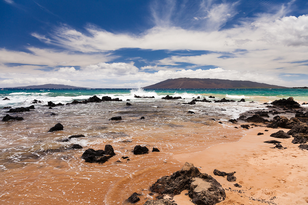 Looking west from this south shore beach shows the splash of slight summer swells along with the west Maui mountains and the Island of Lanai'i.