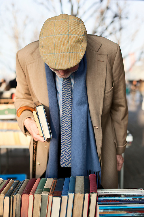 An elderly man shopping in a book market on the Southbank near theNAtional Film Theatre. London, UK. 2012