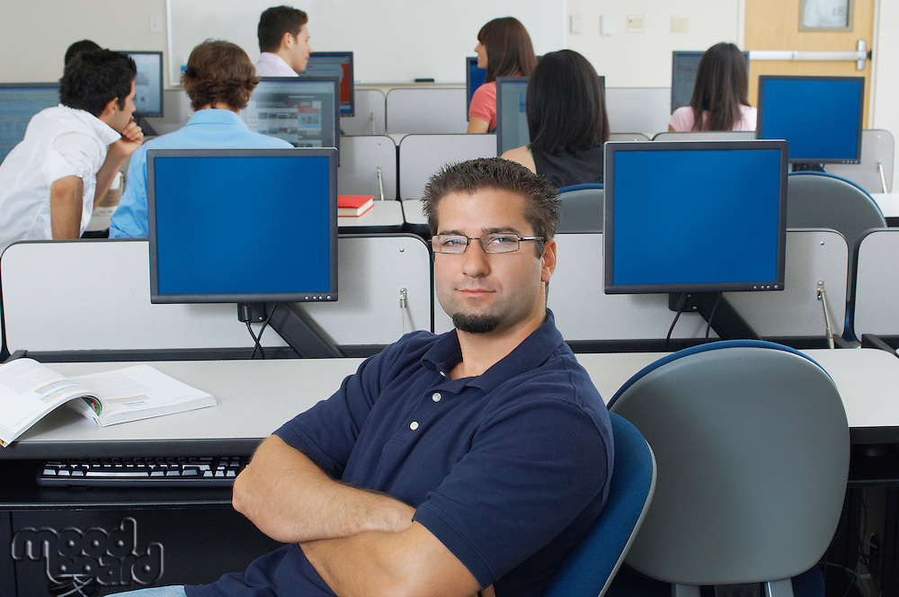 Male student sitting in computer classroom, portrait